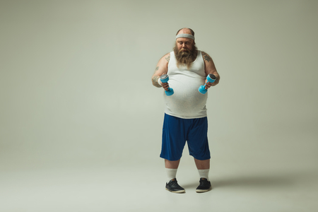 Full length portrait of puzzled fat man looking at dumbbells pensively. Copy space in left side