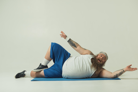 Portrait of crazy thick guy exercising on mat. He is looking at camera with excitement Standard-Bild