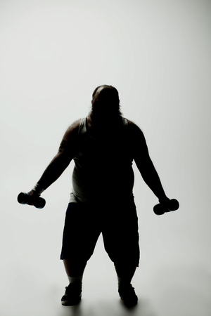 Dark silhouette of strained fat man exercising with weights while standing