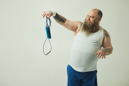 Obese man is staring at skipping rope with aversion. Isolated and copy space