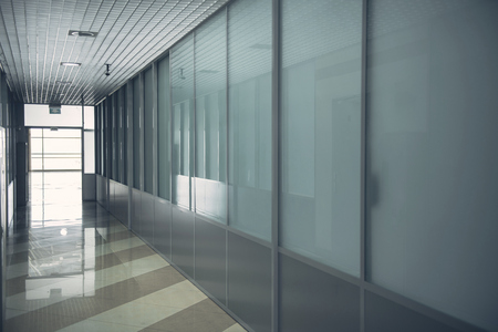 Design of long hallway with glass walls and with window at end of it Banque d'images