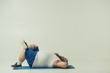 Lazy fat man is resting after workout. He is lying on mat with closed eyes. Copy space