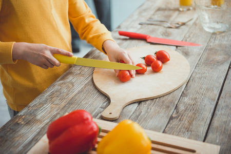 Close up of boy hands slicing vegetables for salad on cooking board