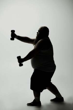 Profile of concentrated fat man with big abdomen standing and lifting dumbbells