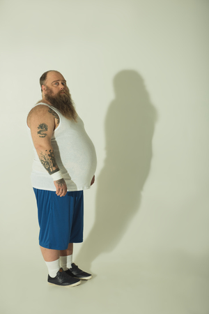 Dreaming of good figure. Dreamful fat man is standing while his shadow is not reflecting his big belly. Copy space