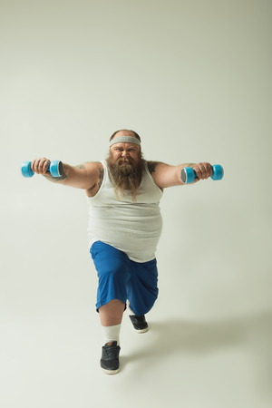 Full length portrait of strained fat man is exercising with dumbbells. He is squatting with effort