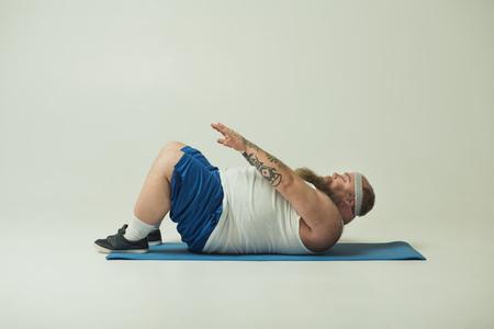 El hombre gordo lento está haciendo abdominales con esfuerzo. El esta acostado en la estera