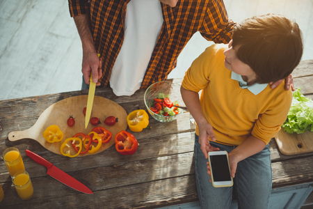 Top view of father and kid spending day in cooking room. Man slicing vegetables and talking to boy. Child sitting on table with smartphone Stockfoto
