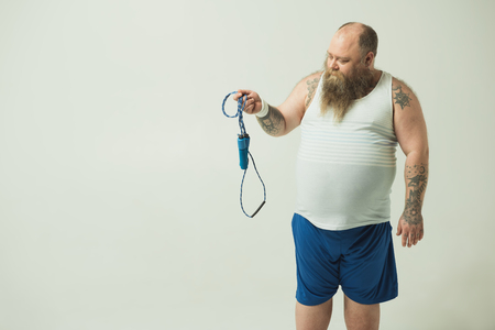 Bearded fat man is standing and looking at skipping rope pensively. Choosing between sport and laziness concept. Isolated and copy space
