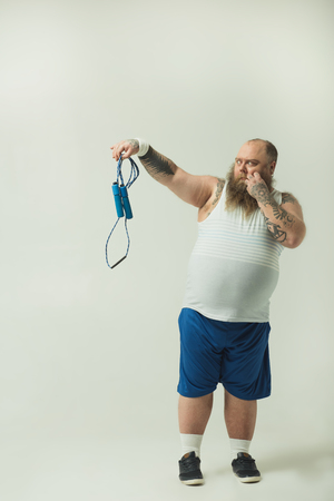 Full length portrait of shocked fat guy is holding a jump rope and looking at it with disgust. Laziness concept Banco de Imagens