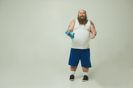 Full length portrait of funny fat man is holding dumbbells and laughing. Copy space Banco de Imagens
