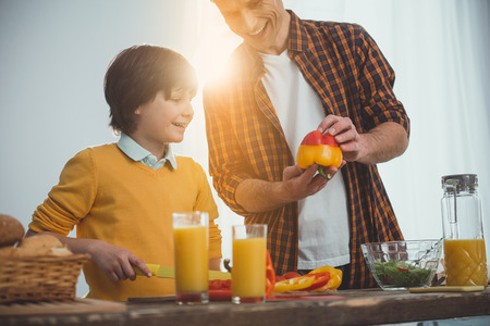 Dad and child preparing salad. Glad man joining two colorful halves of bell peppers. Kid looking at him and smiling