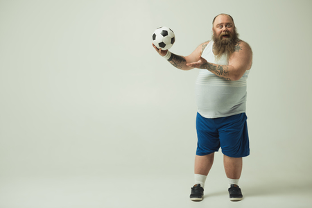 Full length portrait of excited thick man is playing with a ball. He is standing and laughing. Copy space