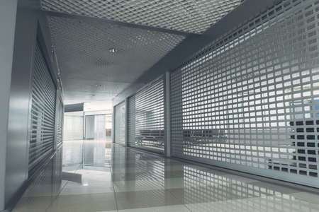 Wide grey long corridor with bright door at end of it Stock Photo