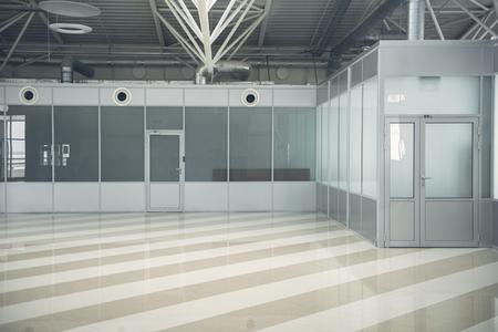 Two grey doors locating in wide hall with striped floor Banco de Imagens