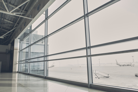 Close up wide window of modern airport hall. Different planes locating on street