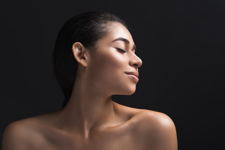 Profile of well cared lady with eyes shut with joy. Isolated on black background