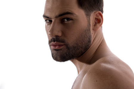 Close up of face of pleasant shirtless bristled guy is standing and looking at camera thoughtfully. Isolated on light background Stock Photo