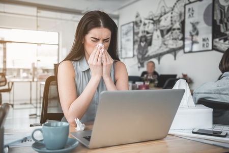 Portrait of disappointed businesswoman blowing nose into handkerchief while using notebook computer. Unhappy sick worker concept Stock Photo