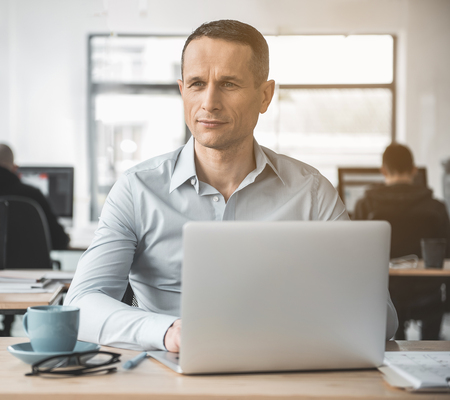 Portrait of pensive worker typing in notebook computer while sitting at table opposite colleagues in office. Contemplative employer during labor concept Stock Photo