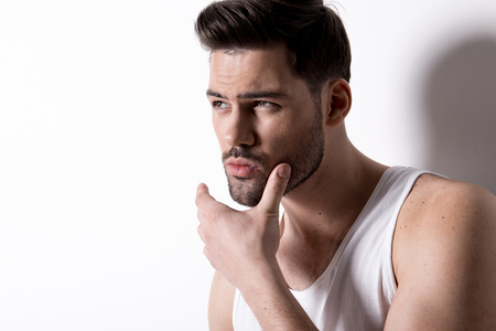 Portrait of stylish young attractive man with stubble is looking aside pensively while touching his face. Copy space in the left side
