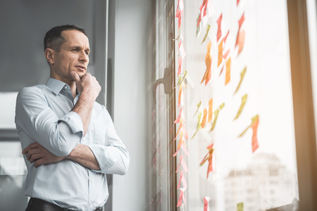 Portrait of pensive businessman touching chin by hand while looking at sticky notes on window.