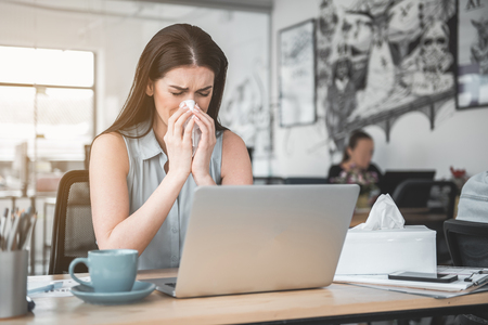 Portrait of frustrated girl blowing nose into handkerchief while working with laptop. Unhappy sick worker concept Stock Photo
