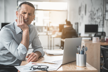 Portrait of disappointed businessman feeling pain in tooth while working with laptop in office. Disease at labor concept Stockfoto