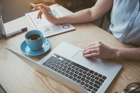Schließen Sie herauf weibliche Hände, die in Notebook-Computer tippen, während Sie Notizen auf Papier machen