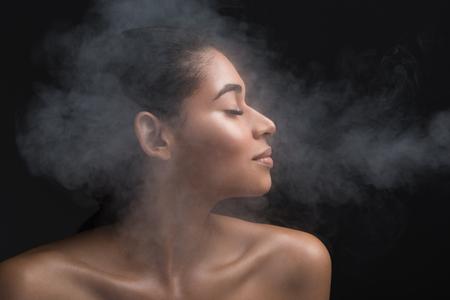 Perfil de mujer guapa con los ojos cerrados olfateando el humo a su alrededor con alegría. Aislado sobre fondo negro