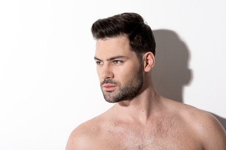 Side view of gorgeous young bearded naked man is standing and looking aside thoughtfully. Copy space in the left side. Stock Photo