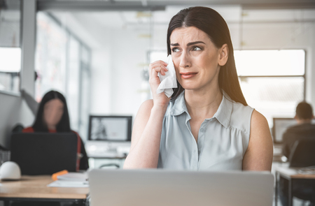 Portrait of young weeping girl facing problems while working in modern office. Trouble at job concept