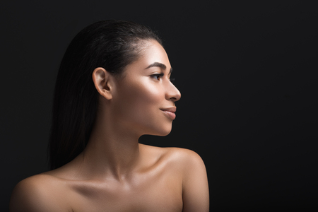 Profile of girl with satisfied expression. Her locks are cared and long. Copy space in right side. Isolated on black background
