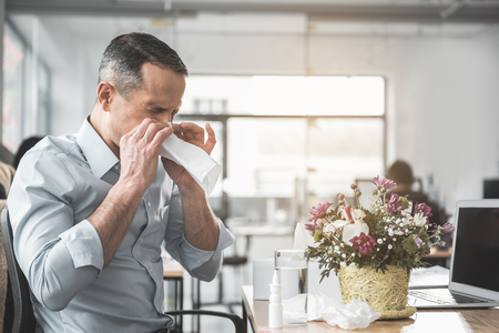 Side view unhappy ill businessman with running nose working with laptop in office. He sitting at table near pretty bouquet. Diseased employer at job concept Stock Photo