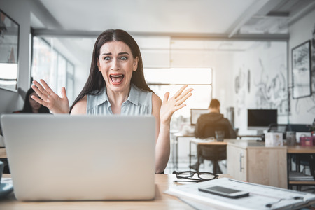 Portrait of screaming businesswoman gesticulating hands while looking at laptop at desk. Problem at job concept