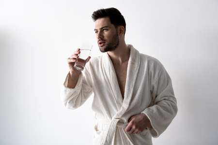 Young attractive bearded man wearing bathrobe is standing with glass of water. He is looking aside thoughtfully. Isolated on light background 스톡 콘텐츠