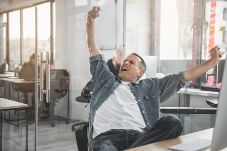 Portrait of beaming man yawning while gesticulating hands. He working in office Imagens