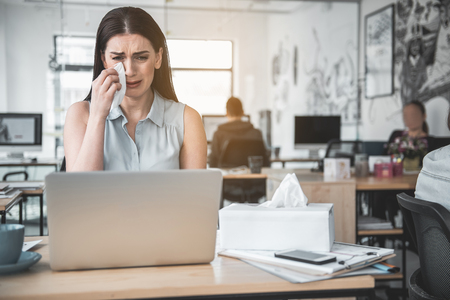 Portrait of crying female wiping away tears with tissue paper while looking at notebook computer. Unhappy worker concept Stock Photo