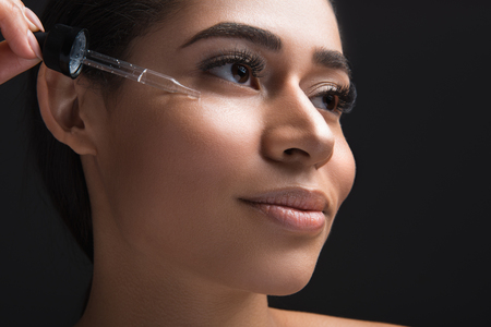 Close up of enjoyed young woman applying anti wrinkle serum on face. Isolated on black background