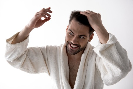 Portrait of cheerful young bristled man in white bathrobe is standing and touching his hair. He is looking aside with smile. Isolated on white background 写真素材