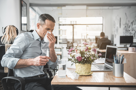Side view frustrated businessman blowing nose into handkerchief while using notebook computer. Unhappy sick worker having allergy concept Standard-Bild