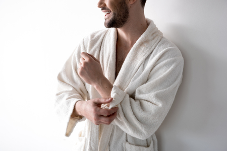 Close up of hands of cheerful male is standing and rolling up sleeves of his bathrobe. He is standing and looking aside with smile