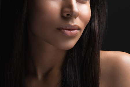 Close up of woman lower face with chubby lips. Her skin is cared and hair loose