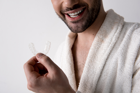 Young happy man with beard and white healthy smile is standing and demonstrating clear aligner for orthodontic correction of bite. Isolated background and close-up
