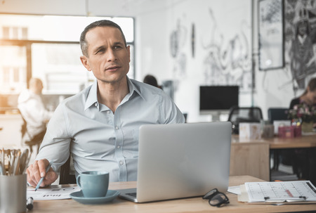 Pensive businessman reading document while typing in notebook computer. He locating at table. Wistful worker at job concept