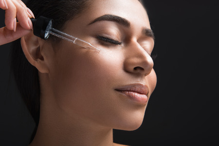Close up of pleased female expression with closed eyes. Woman applying serum oil on facial skin. Isolated on black background
