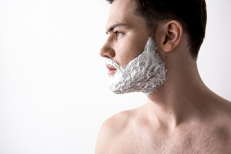 Profile of attractive cute topless guy with shaving foam on his face. He is looking aside thoughtfully. Skin care concept. Isolated with copy space in the left side Stock Photo