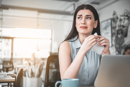 Portrait of crying lady looking away while working in modern office. Sad employer concept