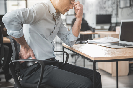 Unhappy weary employer feeling pain in back. He keeping it by hand while sitting at table during labor. Worker with bad state of health concept Standard-Bild