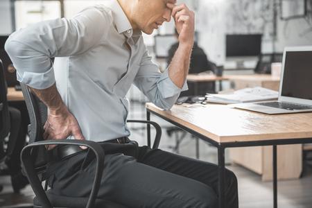 Ongelukkige, vermoeide werkgever die pijn in de rug voelt. Hij houdt het met de hand terwijl hij aan tafel zit tijdens de bevalling. Werknemer met een slechte staat van gezondheid concept Stockfoto